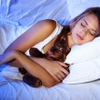 Young beautiful woman with toy bear sleeping on bed in bedroom — Stock Photo #14744795