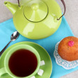Top view of cup of tea and teapot on tablecloths - Stock Photo