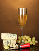 Cheese with mold and goblet of wine on brown background close-up — Stock Photo