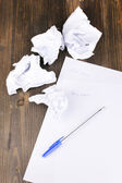 Creation of composition and crumpled sheets on wooden table — Stock Photo