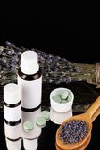 Bottles of medicines and herbs on black background. concept of homeopathy — Stock Photo