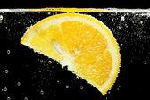 Fatia de laranja na água com bolhas, sobre fundo preto — Foto Stock