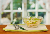 Salad of squid rings, lemon and lettuce in a glass bowl on wooden table close-up — Stock Photo