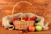 Crop of berries and fruits in a basket on wooden background close-up — Stock Photo