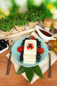 Feta cheese on plate decorated with spices and oil on wooden table close-up — Stock Photo