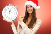 Beautiful young woman with clock, on red background — Stock Photo