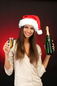 Beautiful young woman with bottle and glass of champagne, on red background — Stock Photo