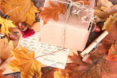 Autumn background: vintage gift, letter and leaves — Stock Photo