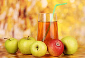 Useful apple juice with apples around on autumn background — Stock Photo