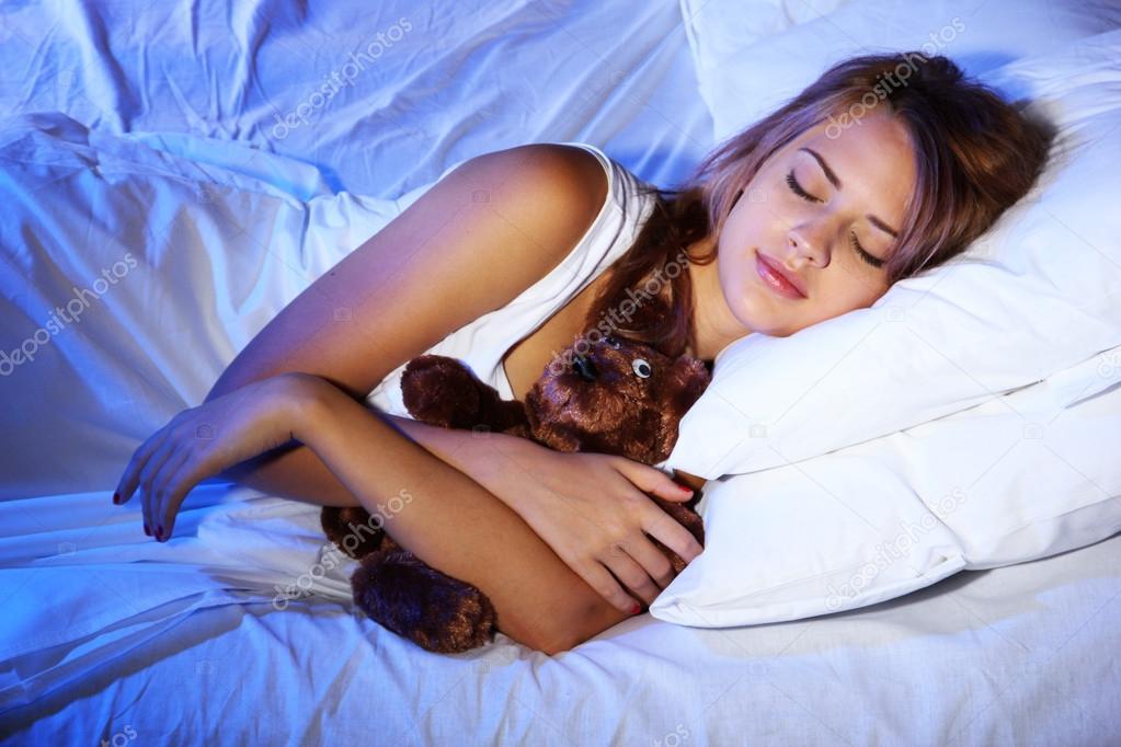 belle jeune femme avec ours jouet dormir sur le lit dans la chambre coucher photo 14744795. Black Bedroom Furniture Sets. Home Design Ideas