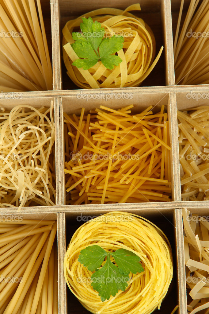 Nine types of pasta in wooden box sections close-up — Stock Photo #14789933