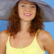 Smiling beautiful girl with beach hat and cocktail on blue background — Stock Photo