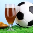 Glass of beer with soccer ball on grass on blue background — Stock Photo