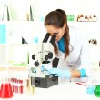 Young scientist looking into  microscope in  laboratory - Stock Photo