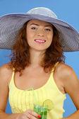 Uśmiechający się piękna dziewczyna z plaży kapelusz i koktajl na niebieskim tle — Zdjęcie stockowe