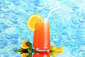 Glass of orange cocktail on blue background — Stock Photo