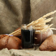 Tankard of kvass and rye breads with ears, on burlap background — Stock Photo #14842543