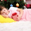 The little girl fell asleep with gift in their hands in festively decorated room — Stock Photo #14848571