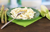 Plate with coleslaw, asparagus and chicory on wooden table on room background — Stock Photo