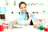 Young female scientist injecting GMO into potato in laboratory — Stock Photo