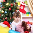 Little girl sitting near the Christmas tree in festively decorated room — Stock Photo #14858393