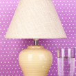 Table lamp and glass of water on purple polka dot background — Stock Photo #14859247