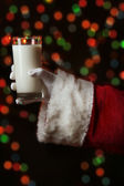 Santa Claus hand holding glass of milk on bright background — Stock Photo