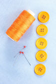 Colorful sewing buttons with thread on blue fabric — Stock Photo