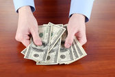 Man recounts dollars on a wooden table close-up — Stock Photo