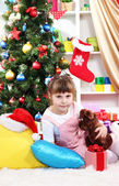 Little girl sitting near the Christmas tree in festively decorated room — Stock Photo