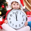 Beautiful little girl with clock in anticipation of New Year in festively decorated room — Stok Fotoğraf #14888951