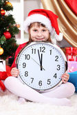 Beautiful little girl with clock in anticipation of New Year in festively decorated room — Foto Stock