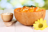 Useful pumpkin porridge in pumpkin on wooden table on natural background — Stock Photo