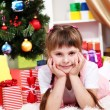 Stock Photo: Little girl near the Christmas tree in festively decorated room