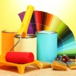 Tin cans with paint, roller, brushes and bright palette of colors on wooden table on yellow background — Stock Photo #14944457