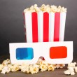 Popcorn and cinema glasses on wooden table on grey background — Stock Photo