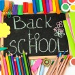The words 'Back to School' written in chalk on the small school desk with various school supplies close-up — Stock Photo #14945567