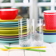 Colorful tableware on wooden table on window background — Stock Photo #14945685