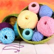 Colorful yarn for knitting in green basket on white wooden table on colorful background — Stock Photo #14945935
