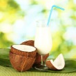 Glass of coconut milk and coconuts on green background close-up — Stock Photo #14945999