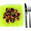 Stock Photo: Roasted chestnuts in the green plate with fork and knife isolated on white