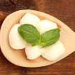 Cheese mozzarella with green basil in wooden spoon on wooden background close-up - Foto Stock