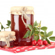 Jars with hip roses jam and ripe berries, isolated on white - Photo