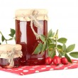 Jars with hip roses jam and ripe berries, isolated on white -  