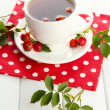 Cup of tea with hip roses, on wooden table -  