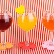 Colorful cocktails with bright decor for glasses on red background with stripes - Stock Photo