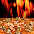 Delicious pizza with seafood on stand on flame background — Stock Photo