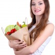 Woman holding a grocery bag full of fresh vegetables isolated on white — Stock Photo