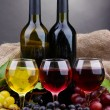 Bottles and glasses of wine and grapes on grey background — Stock Photo #14949215