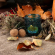 Royalty-Free Stock Photo: Autumnal composition with candle, bottles and leaves on sackcloth background